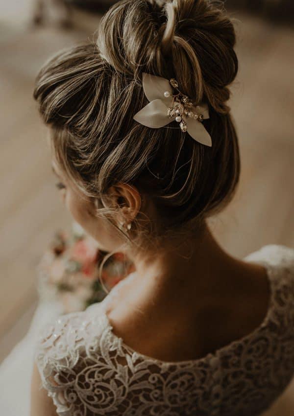 Ein hoher Dutt als Brautfrisur mit schlichtem Haarschmuck