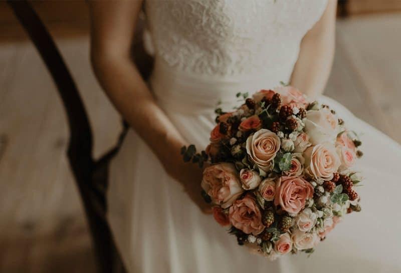 Braut sitzt auf Stuhl und hält Rosenstrauss in Händen