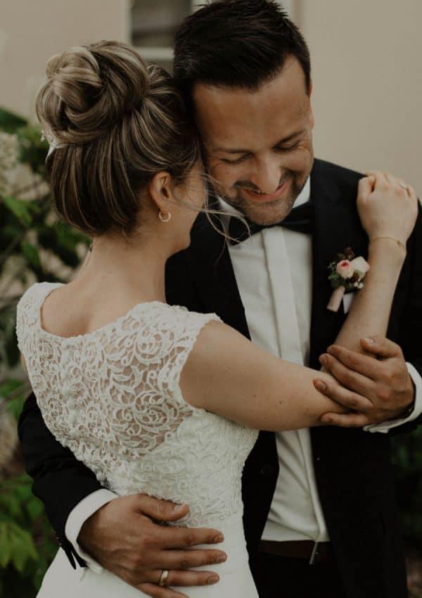 Braut mit hohem Dutt als Brautfrisur schmiegt sich an Bräutigam