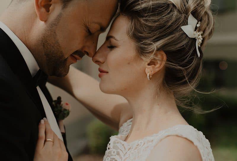 Verliebte Braut mit leichtem Hochzeitsmake-up legt Stirn an Bräutigam