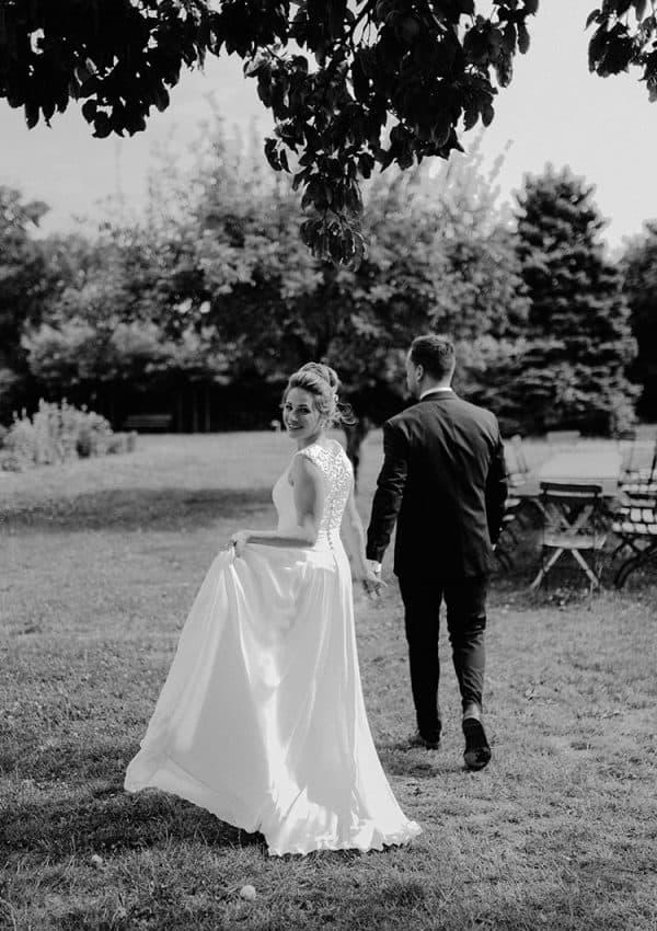 Braut mit einem Brautkleid mit Spitzenrücken läuft in einen Garten