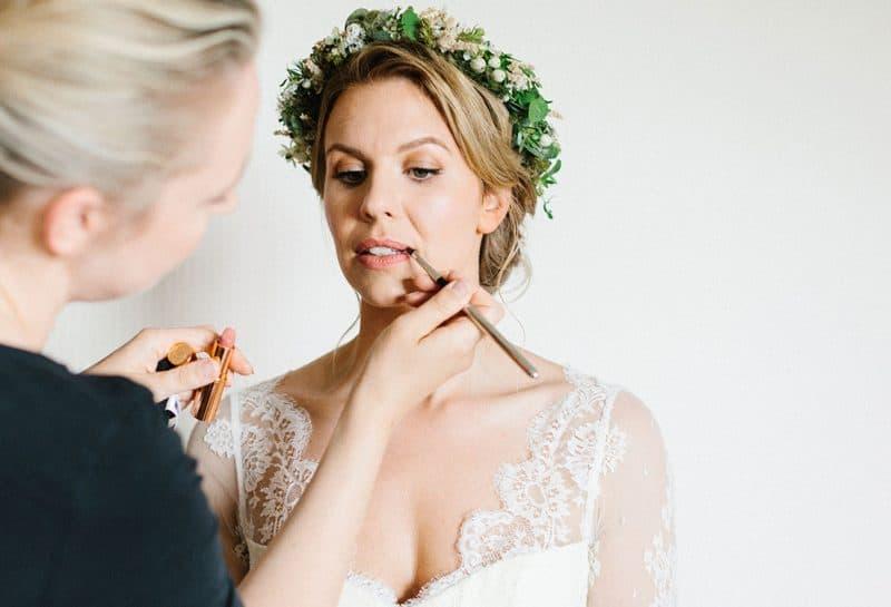 Visagistin frischt Lippenstift bei der Braut auf