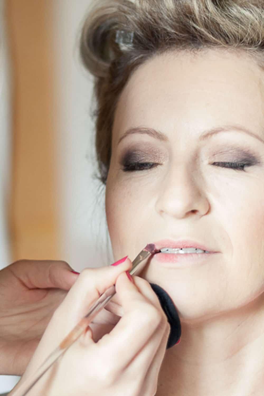 Visagistin probiert Lippenstift an Braut
