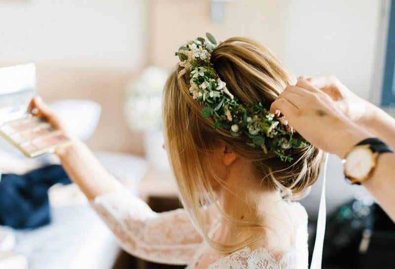 Brautstylistin frischt Lippenstift bei der Braut auf