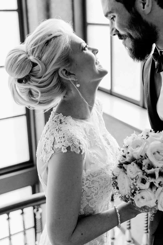 Glückliche Braut mit voluminöser Hochzeitsfrisur
