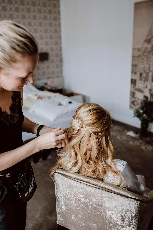 Haarstylistin kreiert eine halb gesteckte Hochzeitsfrisur