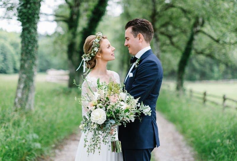 Brautpaar steht auf Feldweg mit großem Blumenstrauss und betrachtet sich