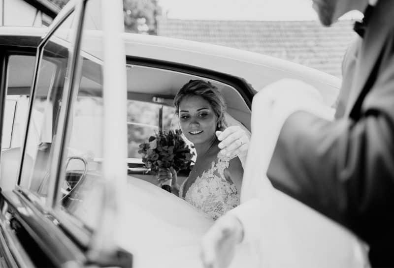 Wunderschöne Braut steigt aus Brautauto
