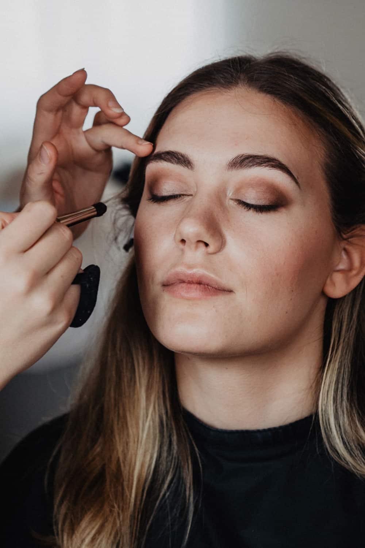 Visagistin schminkt Tages-Make-up für Shooting