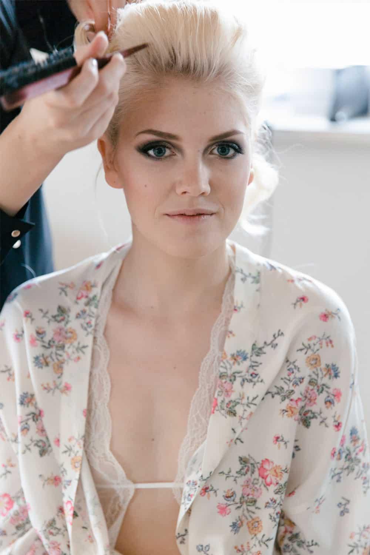 Mobile Haarstylistin steckt Hochzeitsfrisur