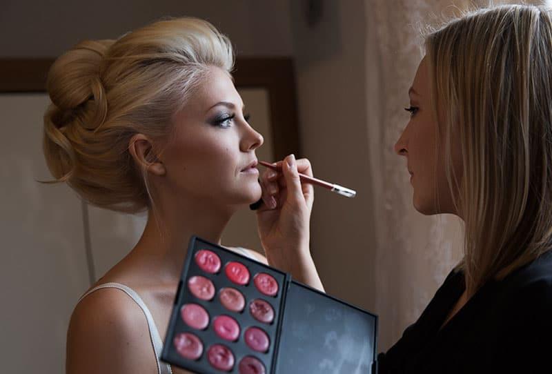 Mobile Visagistin schminkt Braut vor Hochzeit