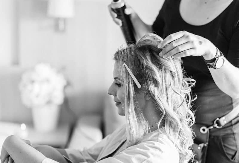Brautstylistin macht entspannter Braut die Hochzeitsfrisur