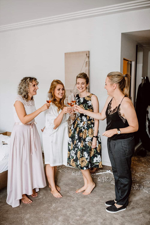 Brautstylistin stößt mit Braut, Trauzeugin und Freundin auf die Hochzeit an