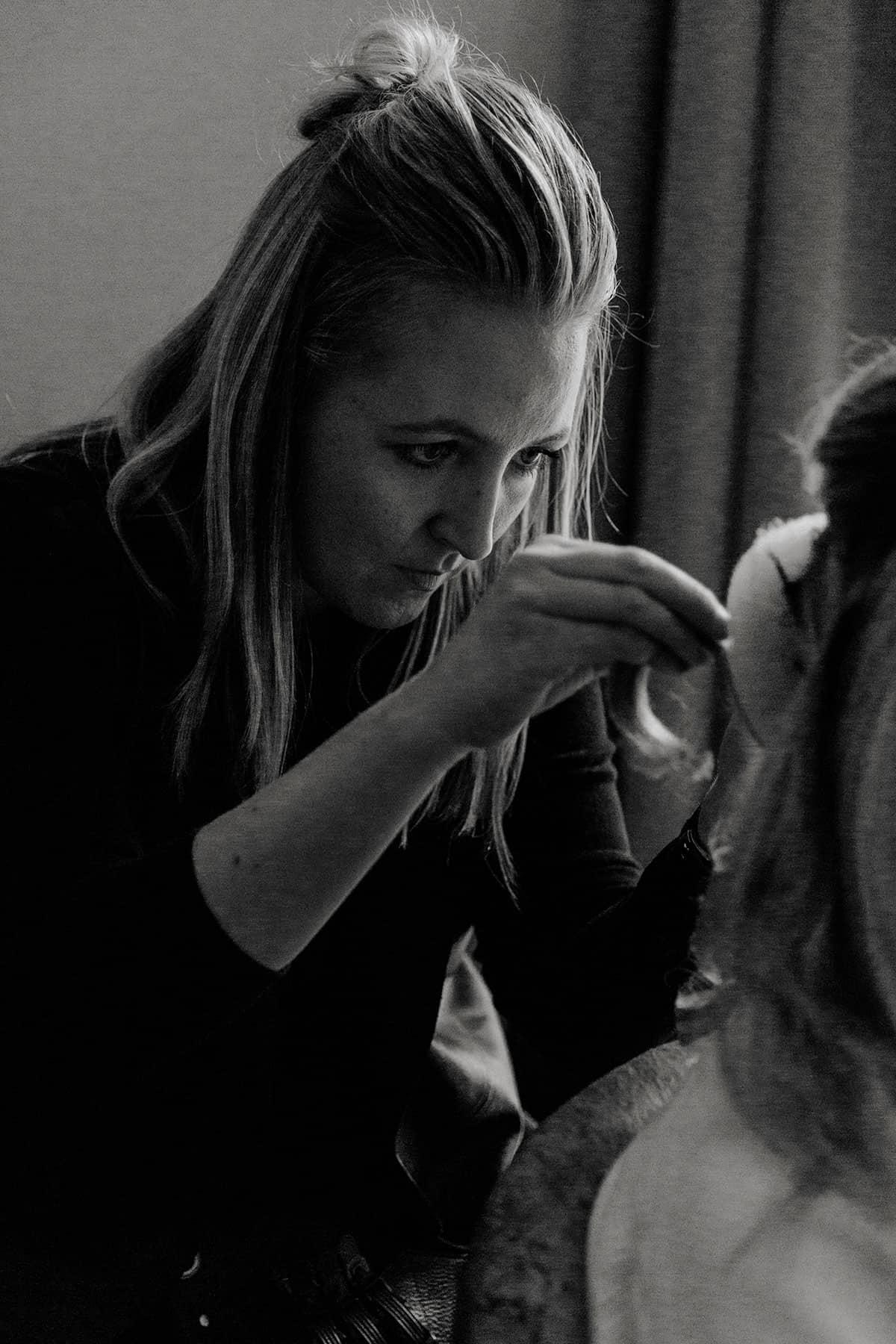 Brautstylistin macht eine Hochsteckfrisur mit Unterbau