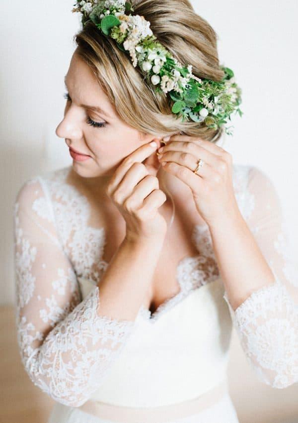Braut blick nach unten und steckt sich Ohrringe an