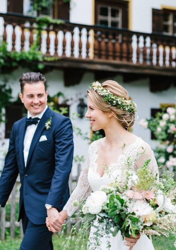Glückliches Brautpaar läuft Hand in Hand vor Bauernhaus