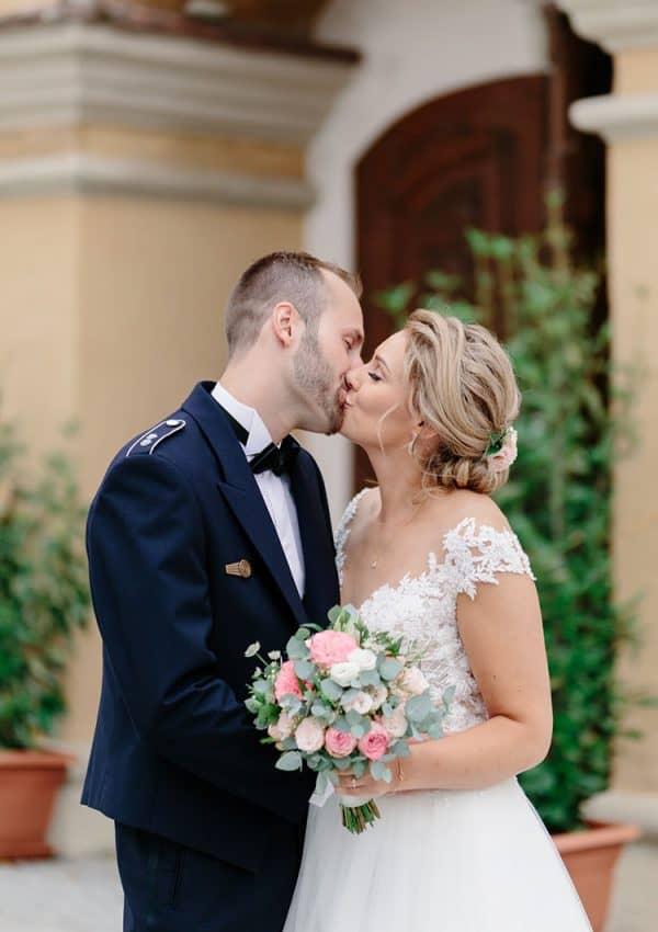 Bräutigam küsst Braut mit eleganter Hochzeitsfrisur