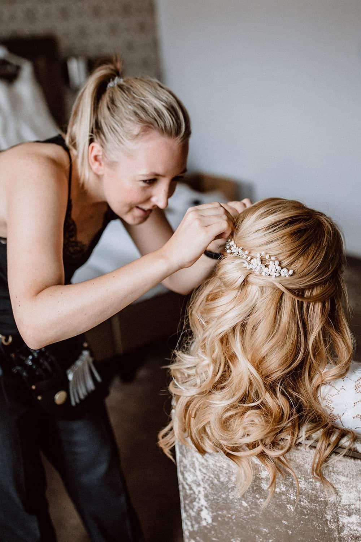 Brautstylistin hat viel Freude beim Styling der Haare