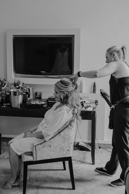 Brautstylistin macht Haarstyling von Braut im Hotelzimmer