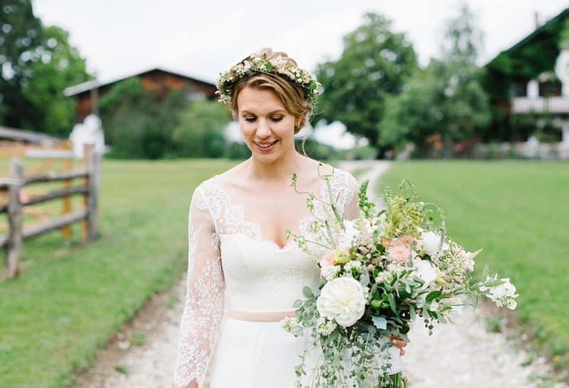Braut mit Blumenkranz läuft vor einer Häuserreihe mit großem Blumenstrauss