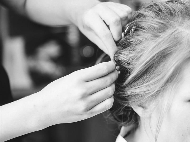 Hairstylistin steckt die Brauthaare hoch