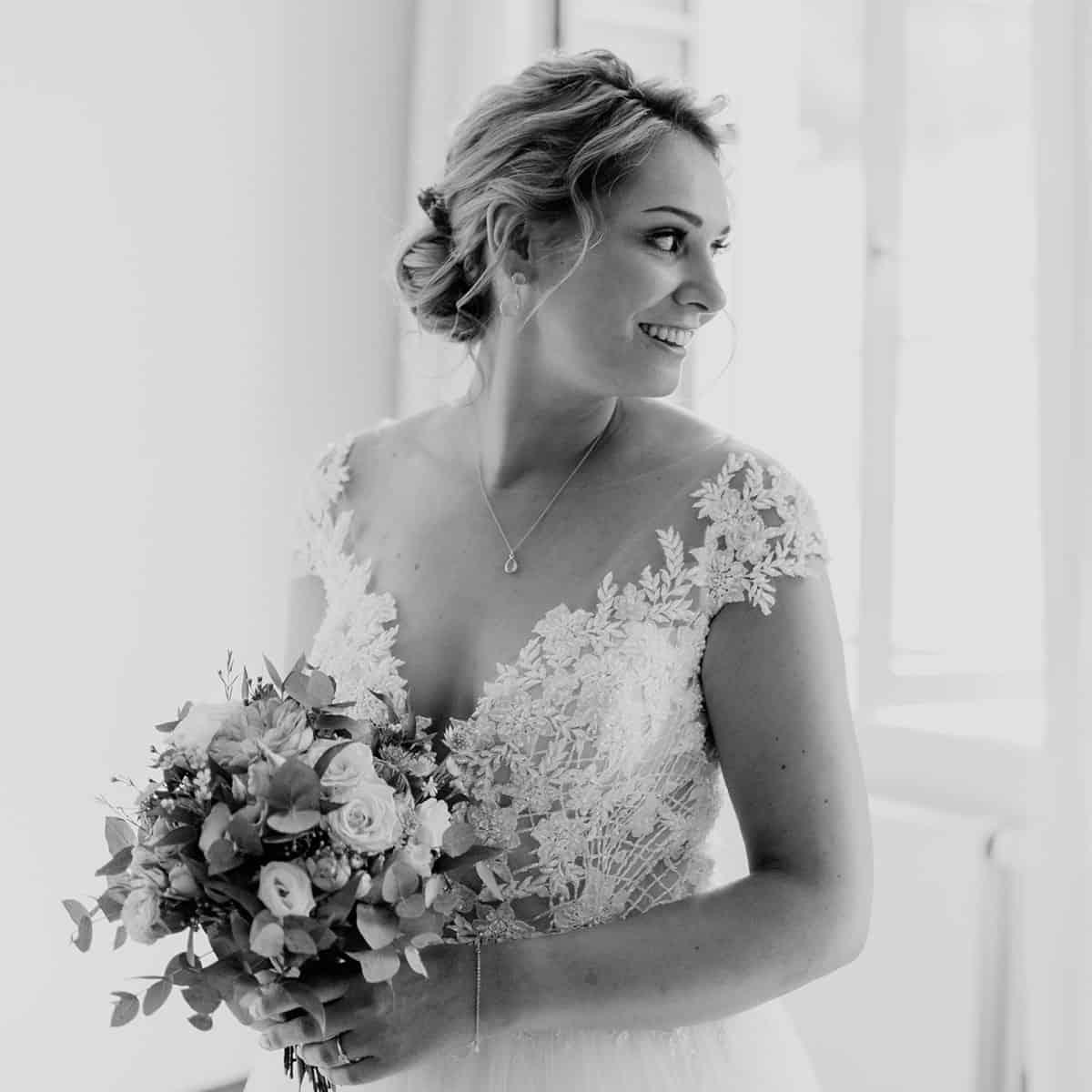 Braut in einem Vintagekleid trägt Hochzeitsfrisur mit echten Blumen
