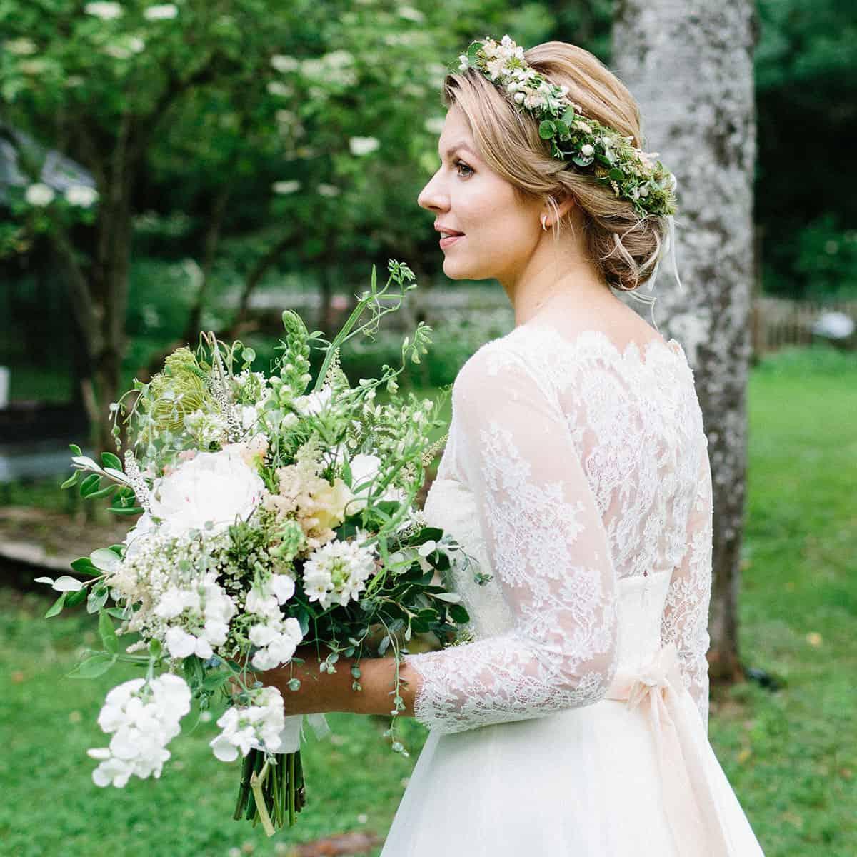 Braut im Spitzenkleid und Seidenschleife trägt Brautfrisur mit Haarkranz