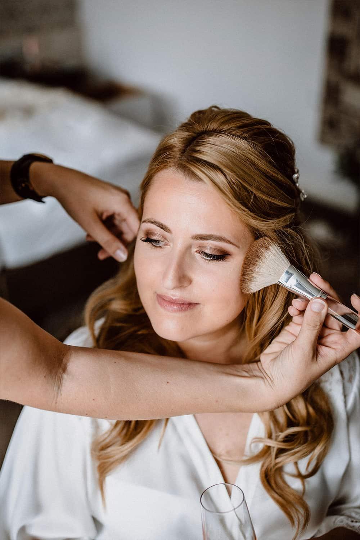 Braut genießt professionelles Make-up von Visagistin