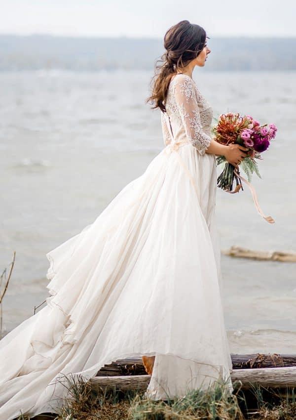 Braut steht im Wasser mit Kleid und Brautstrauss