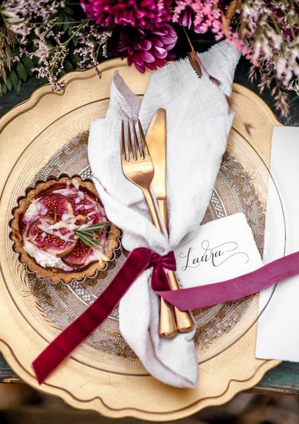 Ein goldener Teller und Besteck von oben mit Seidenband