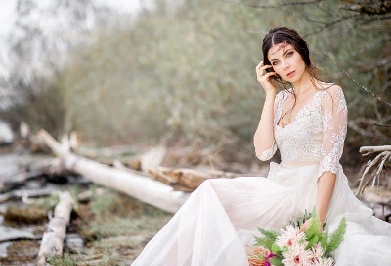 Braut sitzt mit Brautstrauß auf Treibholz am Seeufer